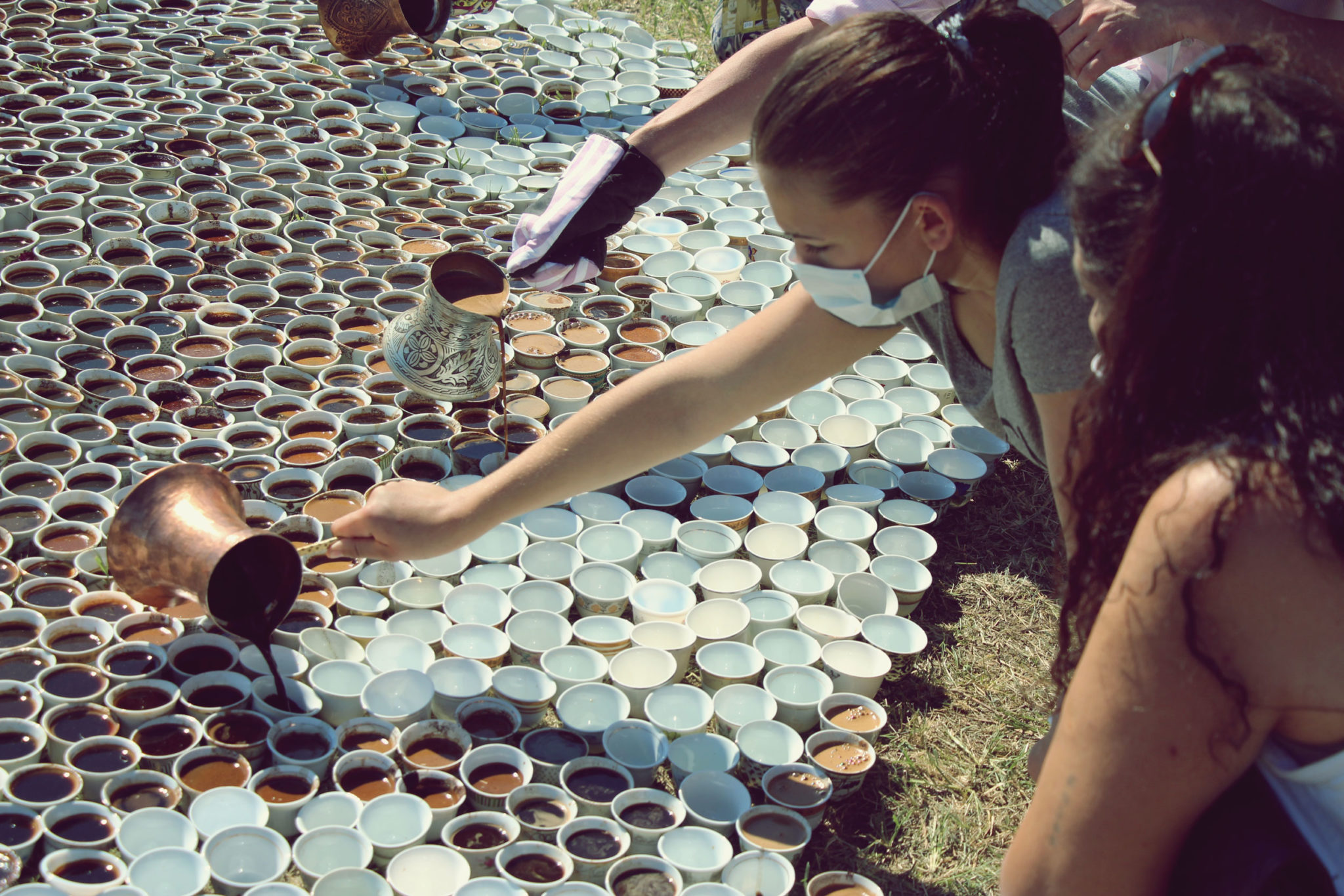 Various people sit on the ground in front of a large number of white cups, more than can easily be counted, that are closely packed together. Roughly half of the cups are filled with a brown liquid. Three people are pouring more coffee from metal containers into cups.